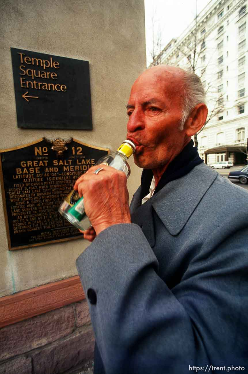 man taking a swig outside of the LDS Temple.
